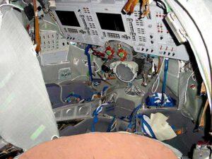 Interiér lodi Sojuz TMA. Snímek pochází ze simulátoru (ve skutečné lodi není poklop v místě, odkud je foceno). Na první pohled jsou patrné dva panely Neptune (displeje v levé a střední části panelu). Periskop (přímo před prostředním sedadlem velitele) je pouze optické zařízení. Zdroj: qsl.net