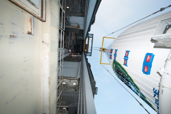Velmi originální perspektiva - napravo aerodynamický kryt připravený k vyzvednutí do montážní věže (nalevo)