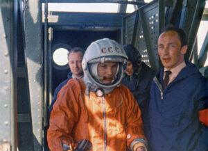 """Gagarin vystupuje z výtahu na nejvyšším patře obslužné věže. Povšimněte si červeného nápisu """"CCCP"""" na helmě."""