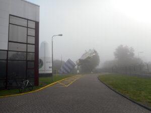 Ráno halila celý areál hustá mlha - na fotce je místo, kde lidé vystupují z autobusů, nebo do nich nasedají - vlevo Space Expo, v pozadí model družice Envisat v životní velikosti.