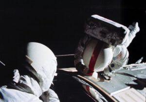 """Ken Mattingly během své EVA. Na helmě má velitelův návlek LEVA s identifikačním červeným pruhem a na zádech """"krabici"""" OPS."""