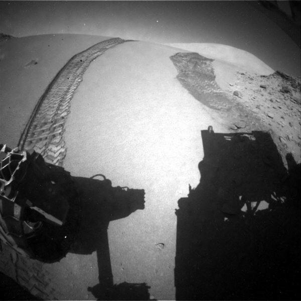 Sol 535 - přejezd písečné úžiny je úspěšně zakončen zaparkováním na pevném skalním podloží. Kamera HazCam snímá stopy kol v písku