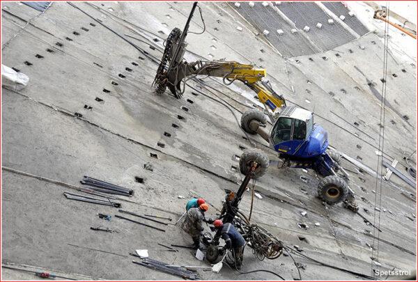 Betonáři finišují na svazích odtokového kanálu.