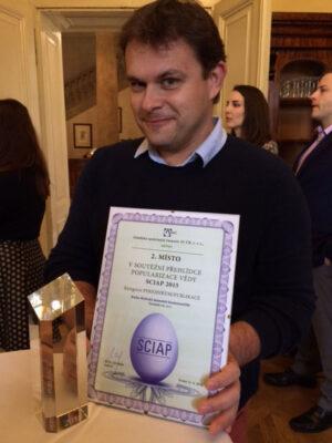 Ondřej Šamárek s diplomem a skleněnou soškou za druhé místo knihy Kritické momenty kosmonautiky v kategorii Časopis/Publikace.