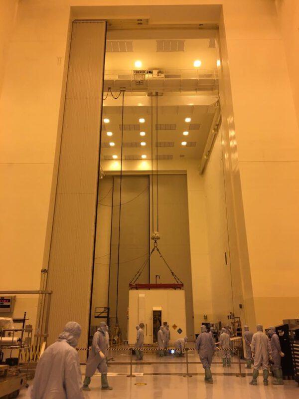 V přechodové komoře před halou PHSF (Payloads Hazardous Servicing Facility) technici zvedli ochranné víko kontejneru