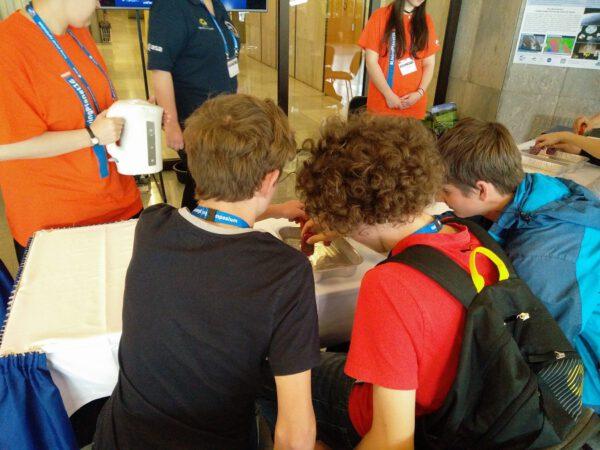 Studenti měří pomocí teploměrů jak proudí teplá voda v kádi se studenou vodou.