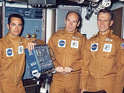 Posádka testu SMEAT (zleva: Crippen, Thornton, Bobko), v popředí nebohý ergometr.