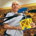 Matthew Golombek z JPL drží v rukou plnorozměrový model projektu Mars Helicopter.