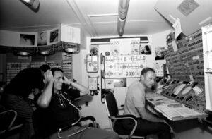 Posádka během výcviku obsluhy komplexu ATM. Ed Gibson s rukama na uších, za ním (jen částečně viditelný) Bill Pogue, u konzoly Jerry Carr.
