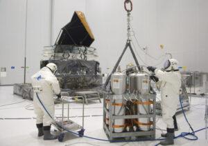 Dva technici v ochranných oblecích tankují hydrazin do teleskopu Planck