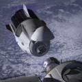 Crew Dragon během připojování k ISS - povšimněte si odklopného krytu v přední části, trunku se solárními panely i stabilizačních ploutví