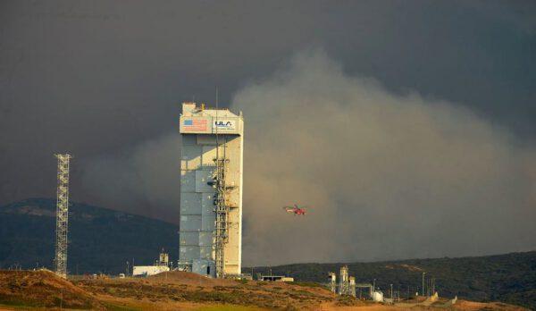 Hasičská helikoptéra a mobilní obslužná věž, ve které se ukrývá raketa Atlas V.