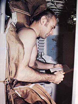 Alan Bean si před spaním čte ve své osobní kajutě