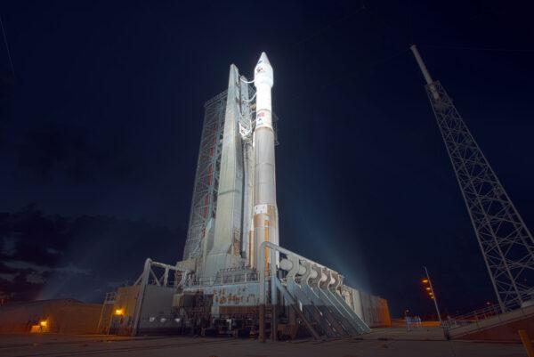 58 metrů vysoká raketa Atlas V se tyčí do noci a silné reflektory osvětlují její povrch.