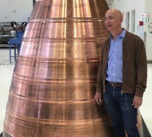 Tryska motoru BE-4 a Jeff Bezos, zakladatel a majitel firmy Blue Origin.