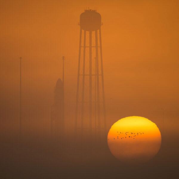 Raketa Antares na startovní rampě v záři vycházejícího slunce