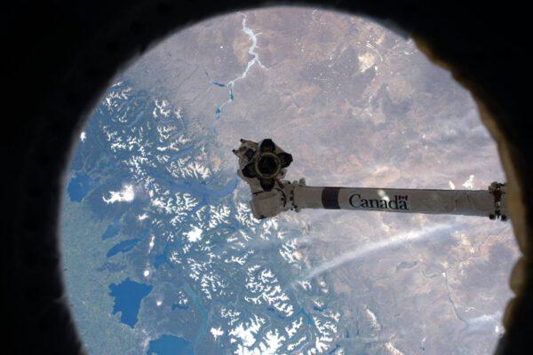 Pohled skrz okno, přes které vidím, že mám přímo proti sobě staniční robotickou paži. Vypadá to, že i ona si užívá pohled na Zemi z výšky 400 kilometrů.
