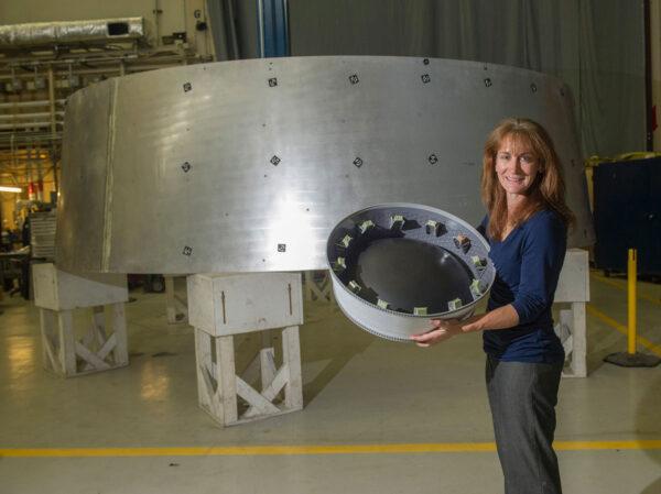 Zmenšený model adaptéru OSA ukazuje jeho závěrečnou podobu včetně schránek na cubesaty, které se při misi EM-1 dostanou k Měsíci. V pozadí vidíme letový exemplář prstence tohoto adaptéru.