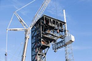 Jeřáb u rampy číslo 41 usazuje k přístupové věži otočnou lávku.