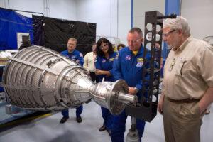 Astronauti Eric Boe, Sunita Williams a Barry Wilmore při obhlídce motoru RL-10. tento typ se použije na horním stupni Centaur rakety Atlas V.