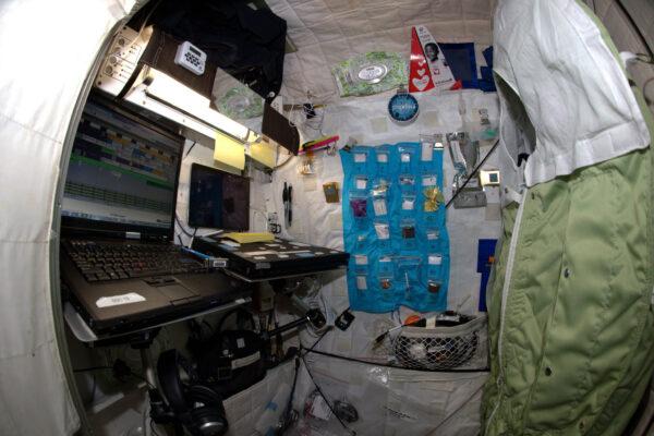 Fotka mé spací komůrky. Je to jediné opravdu soukromé místo na stanici. Prostor je srovnatelný s telefonní budkou, ale poctově se tváří větší – díky stavu beztíže mohu využívat celý objem od podlahy ke stropu. Možná řeknete, ež tu nemám zrovna uklizeno, ale to jste ještě neviděli můj pokoj na Zemi. :-)