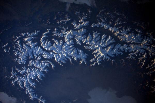 Alpy ve večerním světle. Stíny zvýrazňují údolí a vrcholy. Půjdete letos lyžovat?