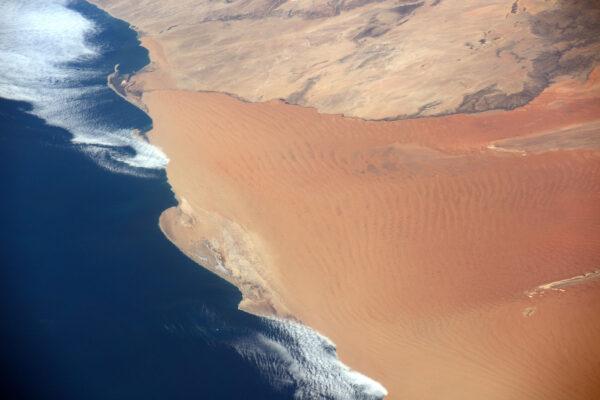 Písečné duny Namibie vypadají, jako kdyby tekly přímo do Atlantiku.