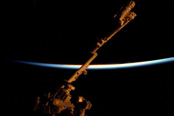 Ve vesmíru nemáme možnost sledovat krajinu při západu slunce. Tak jsem použil mého kamaráda – Canadarm aby mi zapózoval. Mí kamarádi a kolegové mne nabádali, abych zkusil udělat lepší fotku západu slunce, než jaké pořizují oni z paluby letadel. Tady je tedy můj pokus.