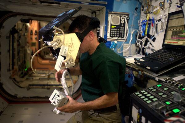"""Když se vydáváme na procházku volným vesmírem, jsme vždy lanem připojeni ke stanici – podobně jako to mají horolezci. Pokud bychom se nedopatřením pustili, lano zabrání tomu, abychom uletěli pryč do vesmírné temnoty. Jako poslední záchranu ale máme ještě na zádech malý tryskový batoh SAFER. Ten používá stlačený vzduch a ovládá se joystickem a s trochou šikovnosti vás dostane zpátky ke stanici. Ale jak už jsem říkal – při výstupu vždy používáme bezpečností lana, takže tryskový batoh je až poslední možností. SAFER se (vyjma zkoušek) nikdy nepoužil při ostré misi a my určitě nechceme být prvními, kdo ho využijí. Ale jak si chcete nacvičit záchranu sebe sama při výstupu pomocí malého jetpacku? Používáme virtuální realitu! Shane (Kimbrough – pozn. překl.) se tu snaží věrně napodobit George Clooneyho z Gravitace. Podobný systém používáme při trénincích na Zemi v Johnsonově středisku. A co vlastně SAFER znamená? Je to :"""" Simplified Aid For EVA Rescue"""". A co znamená EVA? """"ExtraVehicular activity"""" – což označujeme také jako kosmická vycházka. Ano, další akronym v akronymu."""