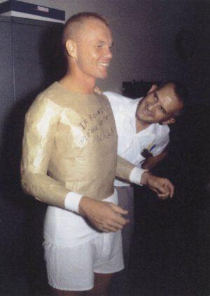 """Inženýři firmy Goodrich berou Glennovi míru na skafandr. Na prsou má nápis """"pokud najdete, vraťte [do] NASA""""."""