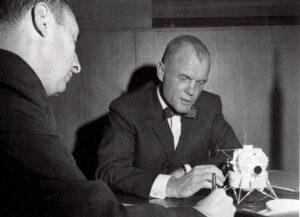 Glenn během rozhovoru s Howardem Benedictem (Associated Press) v únoru 1963: všimněte si modelu lunárního modulu na stole, který měl v prvním návrhu kruhový průlez pro výstup astronautů.