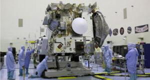 Sonda OSIRIS-REx v montážní hale - návratové pouzdro je objekt kruhovitého tvaru.