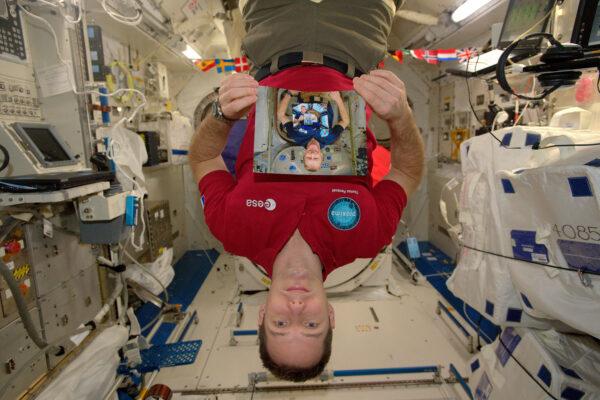 """2/2 Fotka, na které jsem já, jak držím fotku Tima Peaka, který drží fotku Thomase Mogensena, který drží fotku Samanthy Cristoforetti, která drží fotku Alexandra Gersta, který drží fotku Luca Parmitana, který drží fotku … Od našeho jmenování v roce 2009 se všichni členové nové třídy evropských astronautů (říkáme si """"the shenanigans) podívali na Mezinárodní vesmírnou stanici … řekl bych, že si nechali to nejlepší na konec :)"""