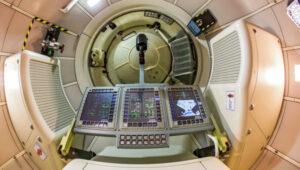 Pohled z pilotní sedačky makety Federace použité při ergonomických zkouškách. Pilotní panel s joystickem je odklopen, za ním je vidět poklop průlezu se stykovacím zařízením.