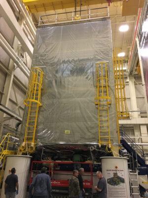 JWST se na této fotce pořízené před vibračními zkouškami ukrývá v ochranném stanu, který jej chrání mimo čistou místnost.