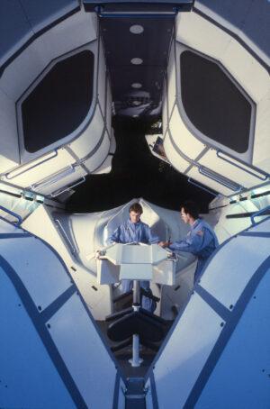 Netradiční návrh společenské části obyvatelného modulu s dominantním jídelním stolem ve středu. Model vypracovala firma Future Systems pro NASA v roce 1988.