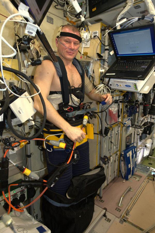 1/2 Oleg je skutečný kosmický muž! Pracoval s opravdu mezinárodním experimentem, který využíval ruský hardware, evropské, americké a ruské astronauty, přičemž studoval pohyb kapalin v tělech astronautů. Tyhle kalhoty, které má na sobě, se jmenují Čibis a jejich úkolem je redukovat tlak ve spodní polovině těla. Tím se krev nasaje zpět do nohou a tedy pryč z hlavy a celkově horní poloviny. Ve vesmíru máme mikrogravitaci a v ní má krev tendenci hromadit se v okolí hlavy. Srdce se totiž pořád snaží bojovat s gravitací, která stahuje tekutiny v našich tělech dolů k Zemi. Tenhle přírodní systém ale nebere v úvahu, že se člověk dostane do vesmíru a tak musíme prozkoumat nové způsoby, jak našim tělům pomoci. Oleg sbírá data do systému Fluid Shifts, který zkoumá, jak mikrogravitace ovlivňuje množství tekutiny v jeho hlavě a očích. Kalhoty Čibis se používají i předtím, než se kosmonauti mají vrátit na Zemi, takže se jejich tělo může začít znovu připravovat na gravitaci.