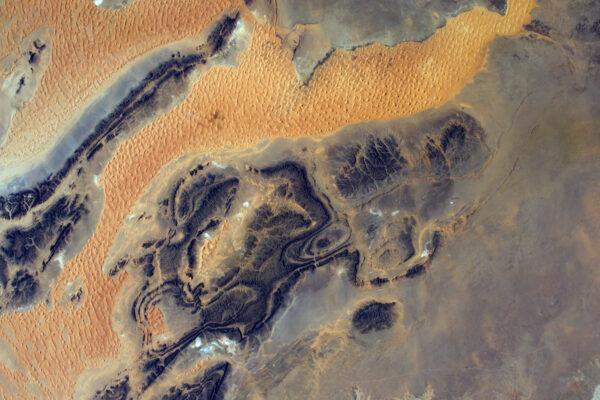 Souboj mezi pískem a skálou je každodenní scénou v poušti a vytváří fantastické abstraktní tvary, které můžeme sledovat z vesmíru.