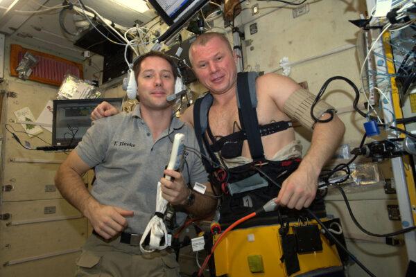 2/2 Oleg je skutečný kosmický muž! Pracoval s opravdu mezinárodním experimentem, který využíval ruský hardware, evropské, americké a ruské astronauty, přičemž studoval pohyb kapalin v tělech astronautů. Tyhle kalhoty, které má na sobě, se jmenují Čibis a jejich úkolem je redukovat tlak ve spodní polovině těla. Tím se krev nasaje zpět do nohou a tedy pryč z hlavy a celkově horní poloviny. Ve vesmíru máme mikrogravitaci a v ní má krev tendenci hromadit se v okolí hlavy. Srdce se totiž pořád snaží bojovat s gravitací, která stahuje tekutiny v našich tělech dolů k Zemi. Tenhle přírodní systém ale nebere v úvahu, že se člověk dostane do vesmíru a tak musíme prozkoumat nové způsoby, jak našim tělům pomoci. Oleg sbírá data do systému Fluid Shifts, který zkoumá, jak mikrogravitace ovlivňuje množství tekutiny v jeho hlavě a očích. Kalhoty Čibis se používají i předtím, než se kosmonauti mají vrátit na Zemi, takže se jejich tělo může začít znovu připravovat na gravitaci.