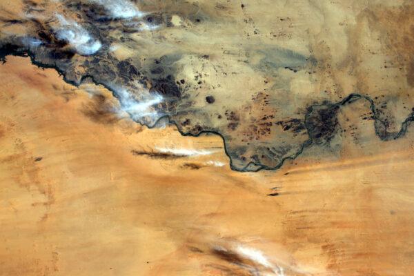 Řeka v Súdánu se zdá jako hranice rozdělující písek od skal.