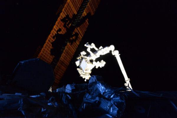 Občas není při výhledu z okna nejlepší pohled na Zemi ale na samotnou Mezinárodní vesmírnou stanici. Robotická paže vrhá stín na solární panely, zatímco zbytek našeho domova ve vesmíru je skryt v temnotě.