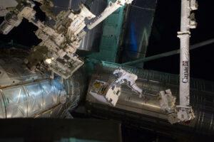Astronaut Mike Fossum při výstupu přenáší experiment RRM.