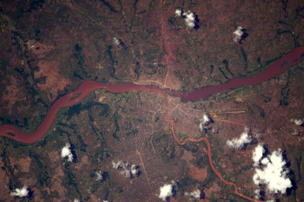 Řeka Kasai protéká v Kongu okolo města Tshikapa. Červenou barvu pravděpodobně způsobují sedimenty. Vypadá to, že mají napravo (na jihu) hezkou letištní ranvej. Líbí se mi, jak cesta nahoře vypadá, jako by vtékala do řeky na druhé straně břehu.