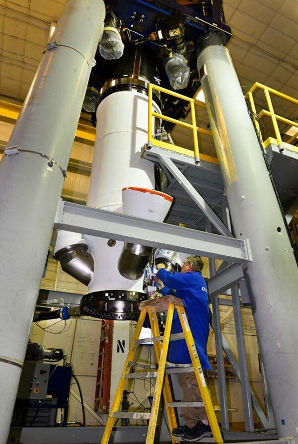 """Technik připravuje testovací exeplář záchranné věžičky lodi Orion - všimněte si """"výfuků"""" nad jeho hlavou."""