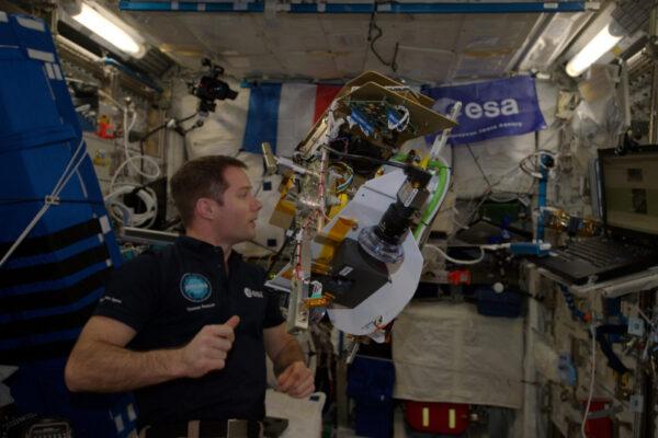 Nastavování experimentu Fluidics. Práce astronauta často zahrnuje kontrolu instrukcí v počítači a teprve potom samotnou práci.
