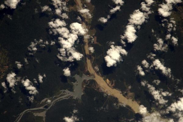 Obří kontejnery v Panamském průplavu jsou zatlačeny do ústraní tropickým lesem.