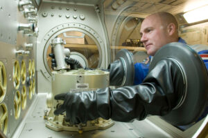 Nizozemský astronaut André Kuipers si nacvičuje práci s gloveboxem v pozemských podmínkách.