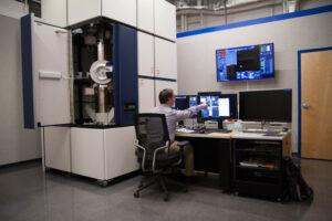 Tom Zega sedí u transmisního elektronového mikroskopu.