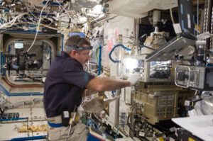 Astronaut Dan Burbank při práci na experimentu ACE na mikroskopické laboratoři Mezinárodní vesmírné stanice. Zdroj: NASA