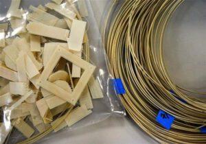 Vlevo plastové díly, vpravo tisková struna.
